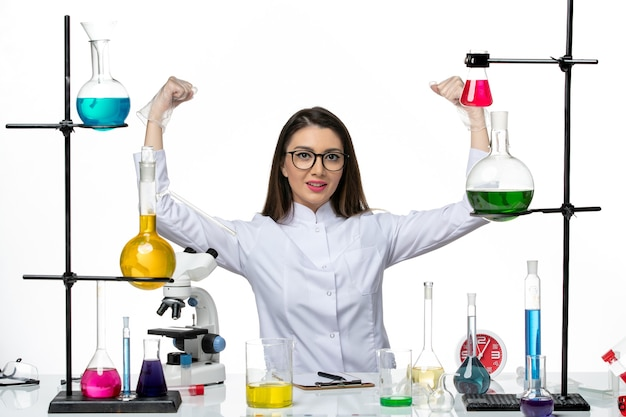 白い背景の科学ウイルスcovidパンデミックラボで屈曲するさまざまなソリューションで座っている白い医療スーツの正面図の女性化学者