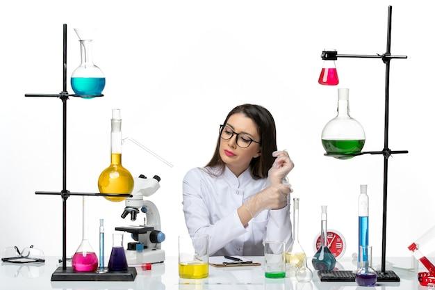 白い背景の科学パンデミックウイルスcovidラボでさまざまなソリューションと一緒に座っている白い医療スーツの正面図の女性化学者