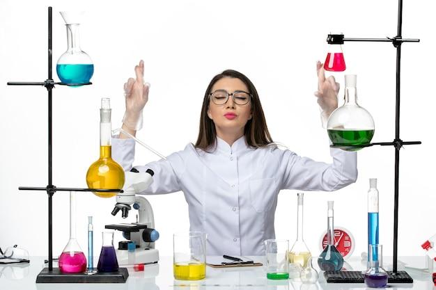 흰색 배경에 다른 솔루션과 함께 앉아 흰색 의료 소송에서 전면보기 여성 화학자 과학 바이러스 실험실 covid 유행성