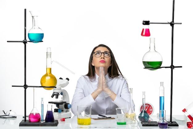 白い背景の科学ウイルスcovidパンデミックラボで祈るさまざまなソリューションと一緒に座っている白い医療スーツの正面図の女性化学者