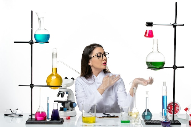 白い背景の科学ウイルス共同パンデミックラボでソリューションと一緒に座っている白い医療スーツの正面図の女性化学者