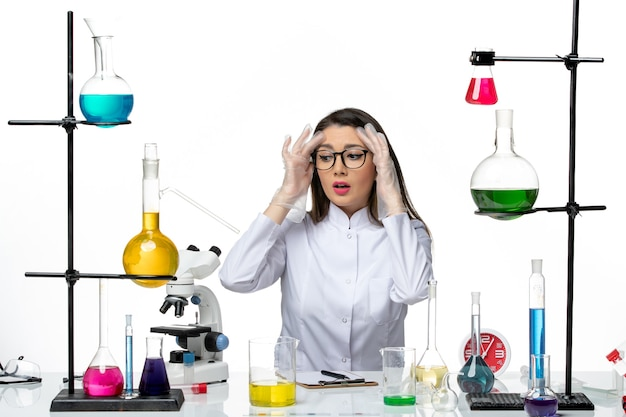 흰색 배경에 솔루션과 함께 앉아 흰색 의료 소송에서 전면보기 여성 화학자 과학 유행성 바이러스 Covid 실험실 무료 사진