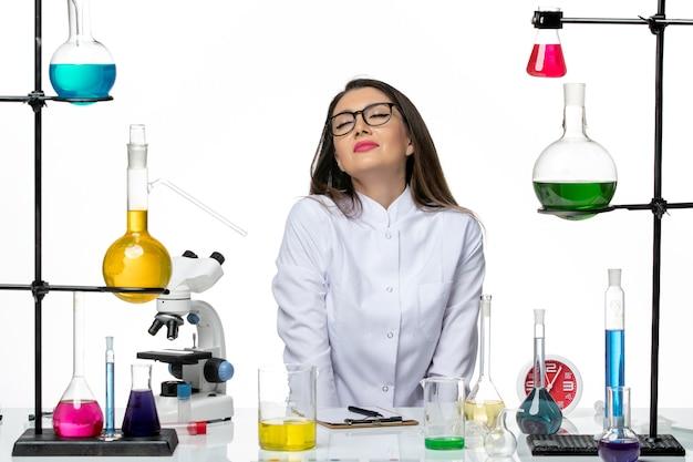 흰색 배경에 솔루션과 함께 앉아 흰색 의료 소송에서 전면보기 여성 화학자 과학 바이러스 실험실 covid 전염병