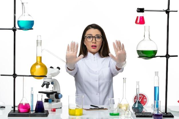 Вид спереди женщина-химик в белом медицинском костюме сидит с растворами на белом столе научная лаборатория пандемического вируса covid