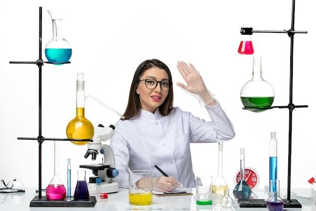 Вид спереди женщина-химик в белом медицинском костюме, сидящая с растворами, написание заметок на белом фоне, научный пандемический лабораторный вирус covid
