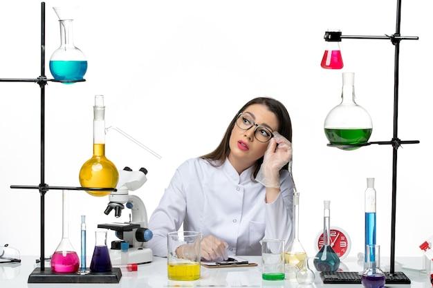 白い背景科学パンデミックウイルスcovidラボにメモを書くソリューションと一緒に座っている白い医療スーツの正面図女性化学者