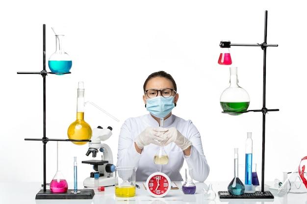Вид спереди женщина-химик в белом медицинском костюме с маской, держащей раствор на белом фоне, химическая лаборатория вируса covid- splash