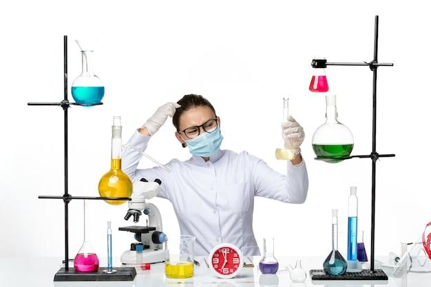 Вид спереди женщина-химик в белом медицинском костюме с маской, держащей раствор на белом столе, химическая лаборатория, вирус covid- splash