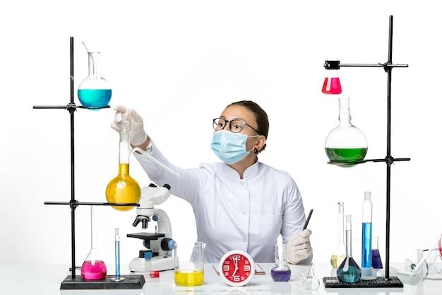 Вид спереди женщина-химик в белом медицинском костюме с маской просто сидит на белом столе химик вирус covid- splash lab