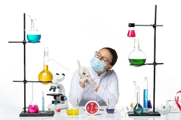 Вид спереди женщина-химик в белом медицинском костюме с маской сидит с растворами на белом столе химик вирус covid- splash lab
