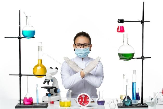 白い背景の化学者ウイルスcovid-スプラッシュラボで禁止サインを示すソリューションと一緒に座っているマスクと白い医療スーツの正面図女性化学者