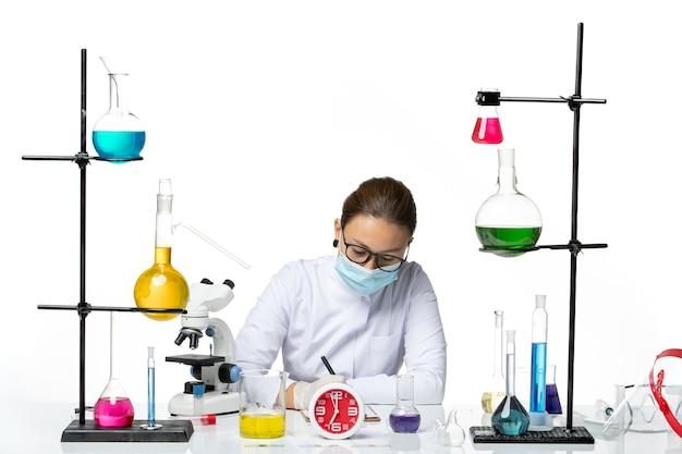 白い背景の化学者ラボウイルスcovid-スプラッシュに書くソリューションと一緒に座っているマスクと白い医療スーツの正面図女性化学者
