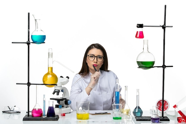 흰색 의료 소송에서 전면보기 여성 화학자 작업 및 흰색 배경에 메모 작성 과학 바이러스 covid- pandemic lab