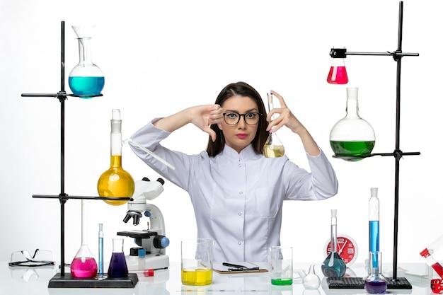 흰색 배경에 솔루션을 사용하는 흰색 의료 소송에서 전면보기 여성 화학자 covid science pandemic lab virus