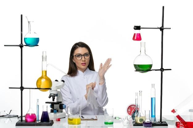 Женщина-химик в белом медицинском костюме, работающая с растворами на белом фоне, вид спереди
