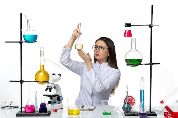 Вид спереди женщина-химик в белом медицинском костюме, работающая с растворами на белом столе, вирус пандемической лаборатории covid science