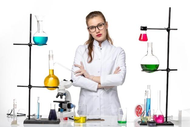 Vista frontale farmacista femmina in tuta medica elegantemente in posa su sfondo bianco chimica virus pandemia covid