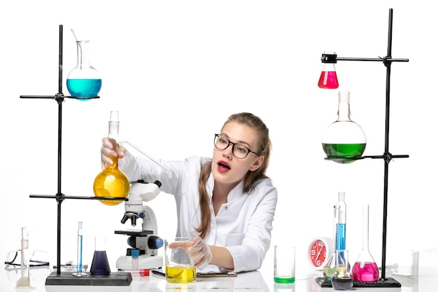 Front view female chemist in medical suit in front of table with solutions on light-white background chemistry pandemic covid- virus