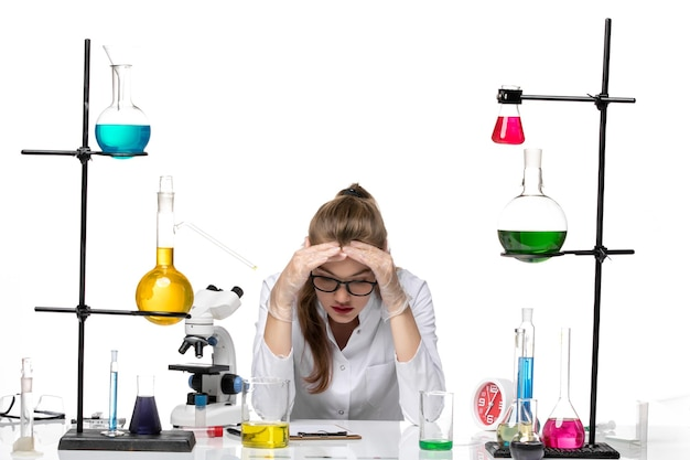 Front view female chemist in medical suit in front of table with solutions on a white background chemistry pandemic covid- virus