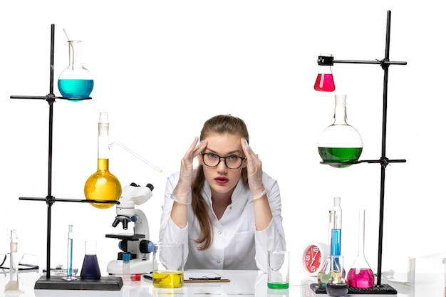 Front view female chemist in medical suit in front of table with solutions on white background chemistry pandemic covid- virus