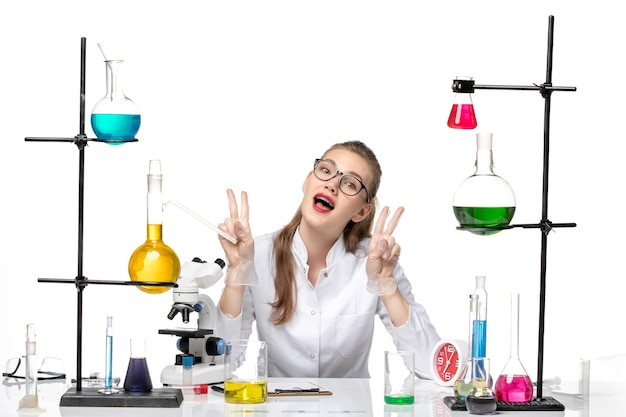 Front view female chemist in medical suit in front of table with solutions on white background pandemic chemistry covid- virus
