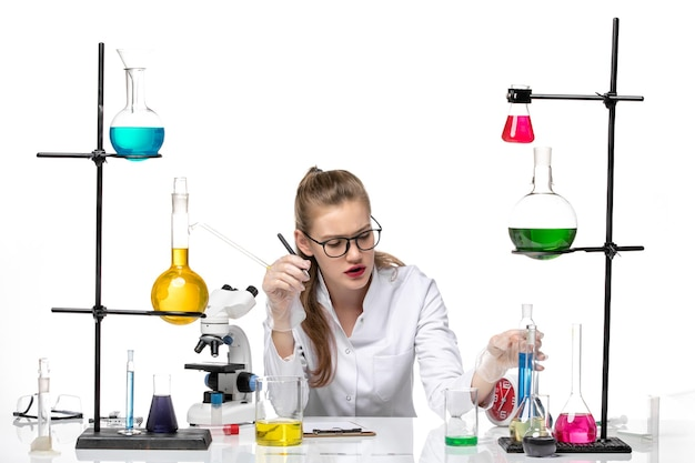 Front view female chemist in medical suit holding flask on white background chemistry pandemic health covid