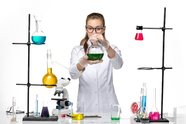 Front view female chemist in medical suit holding flask with green solution on light white background chemistry pandemic covid virus