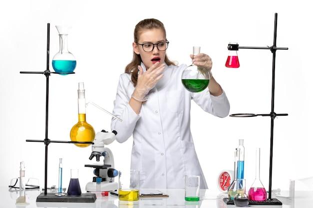 Chimico femminile di vista frontale in vestito medico che tiene boccetta con soluzione verde su sfondo bianco virus pandemico covid di chimica