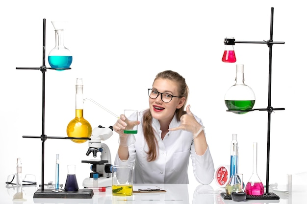 Front view female chemist in medical suit holding flask with solution on the white background chemistry pandemic health covid