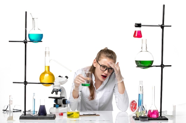 Front view female chemist in medical suit holding flask with solution on white background chemistry pandemic health covid