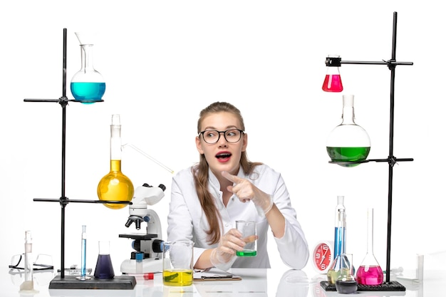 Front view female chemist in medical suit holding flask with solution on white desk chemistry pandemic health covid