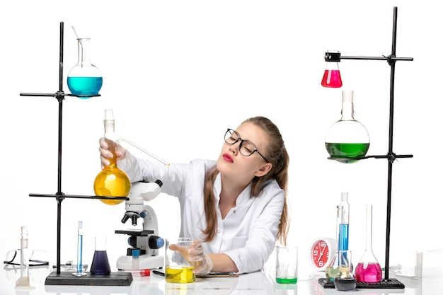 Front view female chemist in medical suit holding flask with yellow solution on a white background chemistry pandemic covid- virus