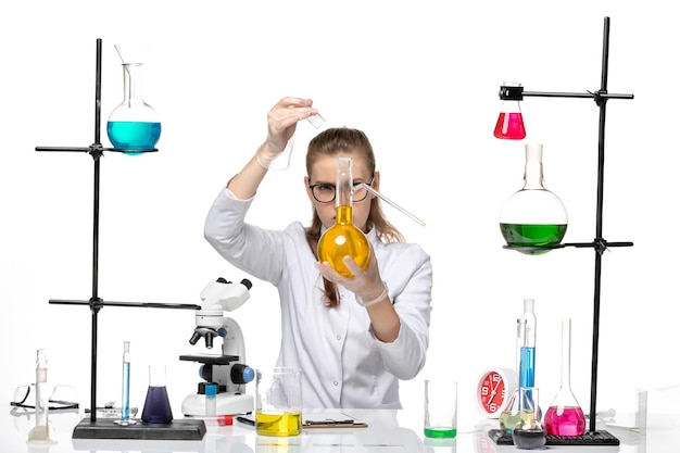 Front view female chemist in medical suit holding flask with yellow solution on white background chemistry pandemic covid virus