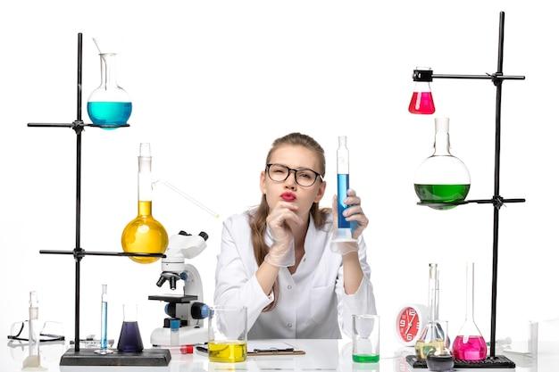 Vista frontale farmacista femmina in tuta medica tenendo lungo pallone con soluzione su sfondo bianco chiaro chimica pandemia salute covid