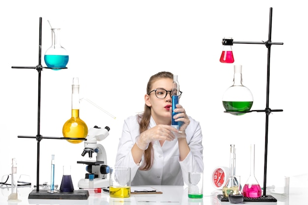 Front view female chemist in medical suit holding long flask with solution on the white background chemistry pandemic health covid