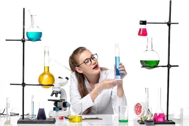 Farmacia femminile di vista frontale in vestito medico che tiene il pallone lungo con la soluzione su fondo bianco covid di salute di pandemia di chimica