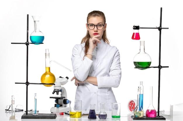 Chimico femminile vista frontale in tuta medica solo in posa su sfondo bianco pandemia di chimica covid-virus