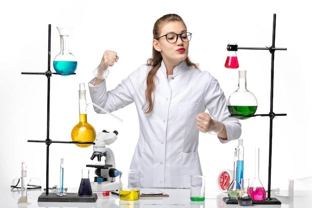 Chimico femminile di vista frontale in vestito medico che posa appena sulla covid pandemia di virus di chimica dello scrittorio bianco