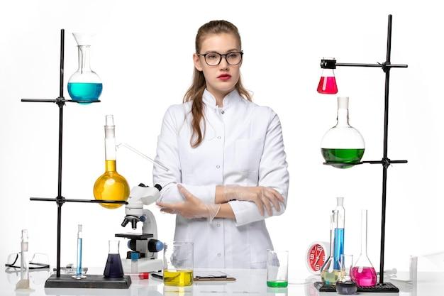 Vista frontale farmacista femmina in tuta medica guardando a distanza sulla scrivania bianca chimica virus pandemia covid