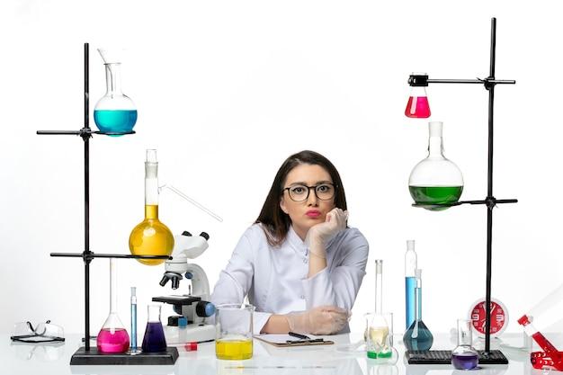 Chimico femminile di vista frontale in vestito medico che si siede intorno al tavolo con soluzioni su fondo bianco scienza pandemica covid virus di laboratorio