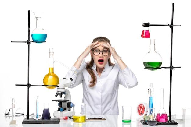 Chimico femminile vista frontale in tuta medica seduta con soluzioni su sfondo bianco pandemia di chimica covid-virus