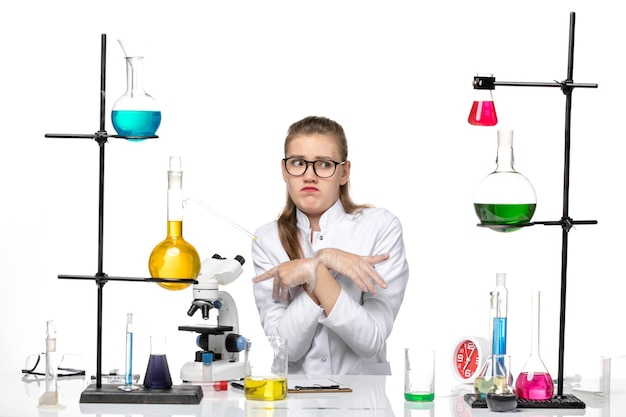 Front view female chemist in medical suit sitting with solutions on the white background pandemic chemistry covid- virus
