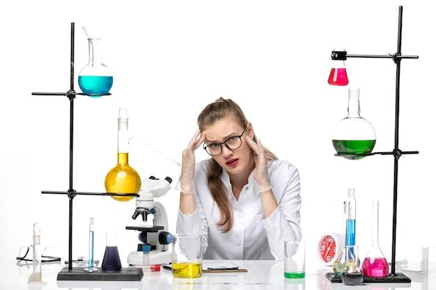 Chimico femminile di vista frontale in vestito medico che si siede con le soluzioni sul virus covid di chimica pandemica dello scrittorio bianco