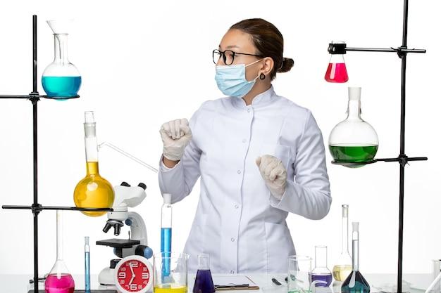 Chimico femminile di vista frontale in vestito medico che si leva in piedi sulla spruzzata di covid del laboratorio di chimica del virus del fondo bianco
