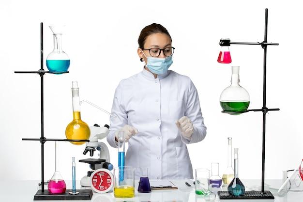 Chimico femminile di vista frontale in vestito medico e maschera da portare sul laboratorio di chimica del virus del pavimento bianco covid- splash