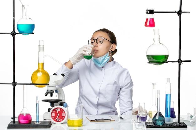 Chimico femminile di vista frontale in vestito medico con la soluzione bevente della maschera su fondo bianco covid chimica del virus del laboratorio della spruzzata
