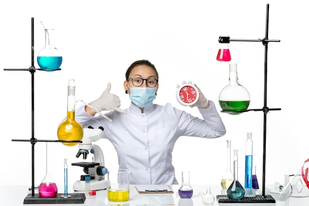 Front view female chemist in medical suit with mask holding clocks on light white background virus lab chemistry covid- splash
