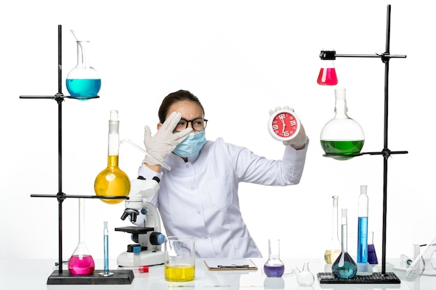 Front view female chemist in medical suit with mask holding clocks on light white background virus lab chemistry covid splash