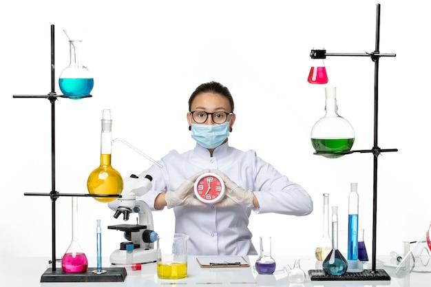 Chimico femminile di vista frontale in vestito medico con la maschera che tiene gli orologi sullo splash covid di chimica del laboratorio del virus del fondo bianco chiaro