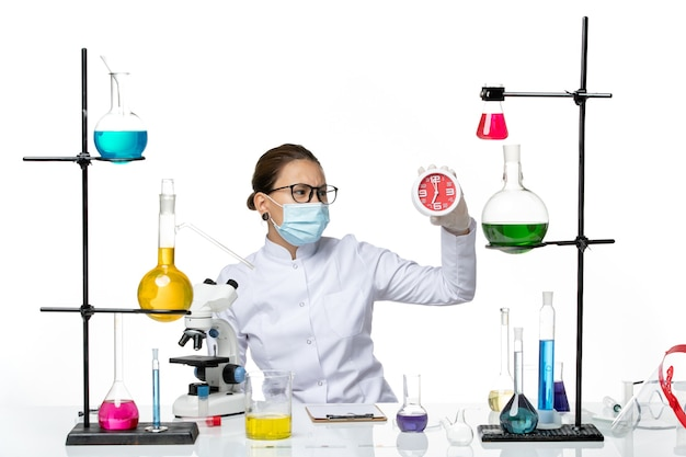 Front view female chemist in medical suit with mask holding clocks on white background virus lab chemistry covid splash